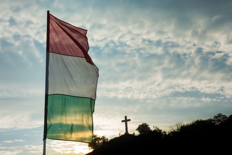 Bandera húngara con la cruz cristiana foto de archivo