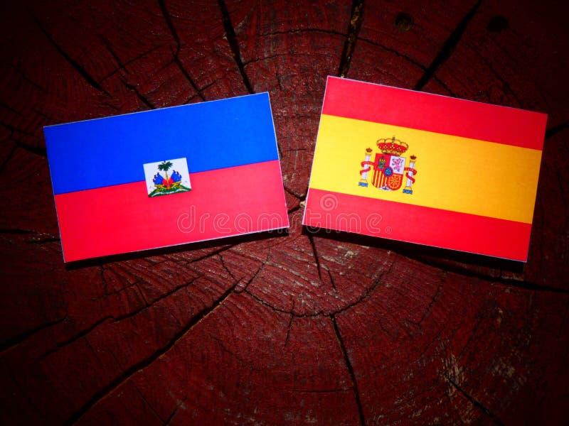 Bandera haitiana con la bandera española en un tocón de árbol imagen de archivo libre de regalías