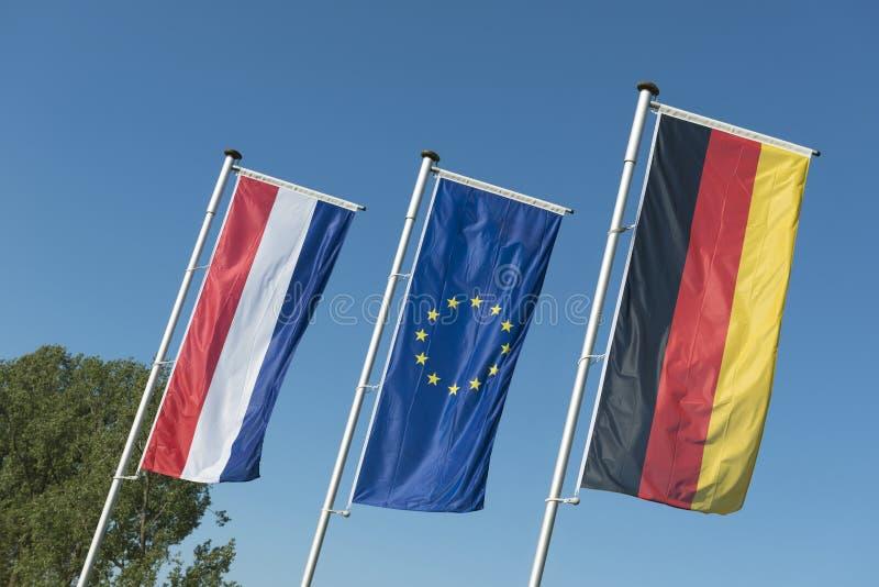 Bandera holandesa, bandera de unión europea y bandera alemana imagen de archivo libre de regalías