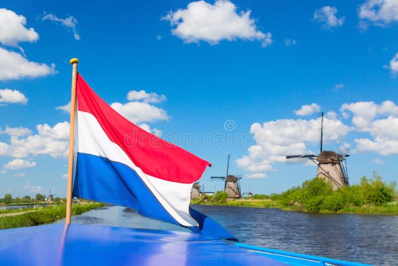 Bandera holandesa que agita en un barco de cruceros contra los molinoes de viento famosos en el pueblo de Kinderdijk en Holanda L fotos de archivo
