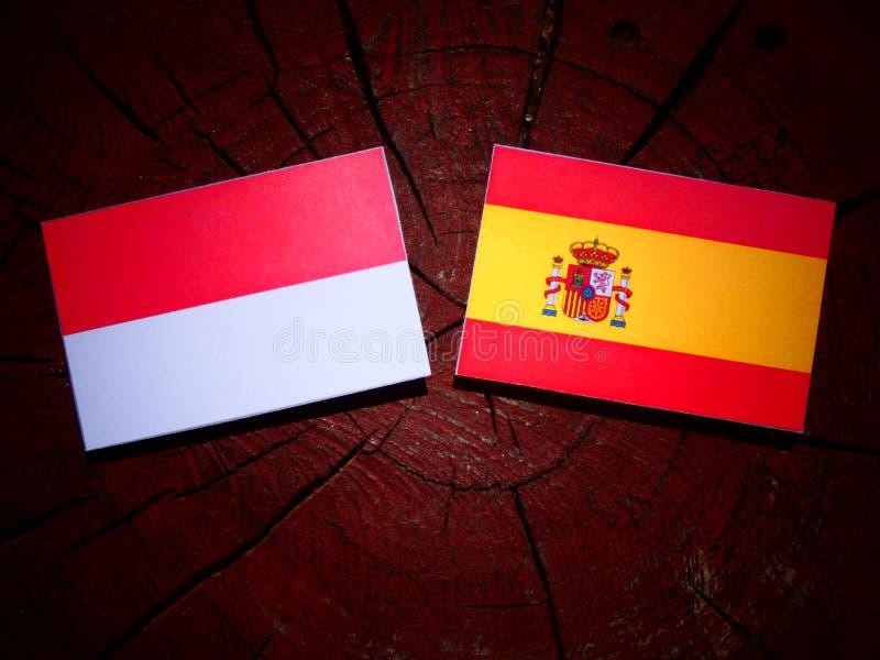 Bandera indonesia con la bandera española en un tocón de árbol fotos de archivo