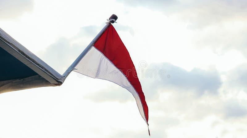 Bandera indonesia que agita en un barco en la playa de Prigi en Día de la Independencia fotografía de archivo