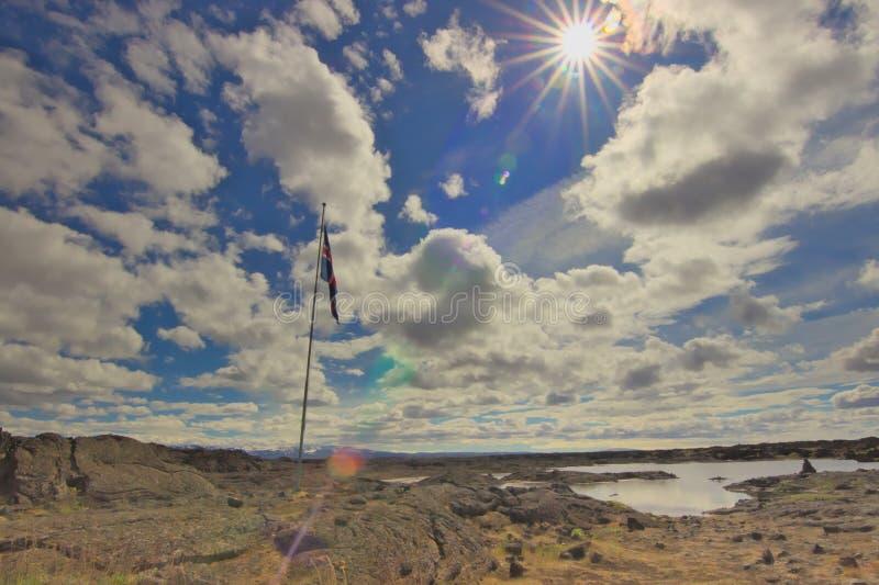 Bandera islandesa en un campo de lava durante un día soleado imagenes de archivo