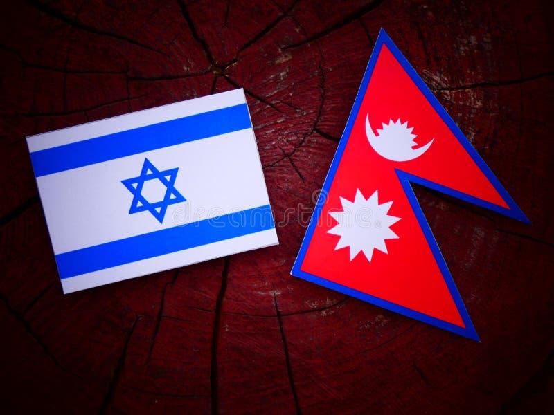 Bandera israelí con la bandera del Nepali en un tocón de árbol aislado fotografía de archivo