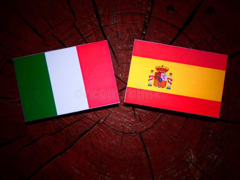 Bandera italiana con la bandera española en un tocón de árbol fotografía de archivo