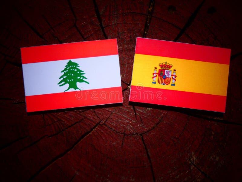 Bandera libanesa con la bandera española en un tocón de árbol foto de archivo libre de regalías