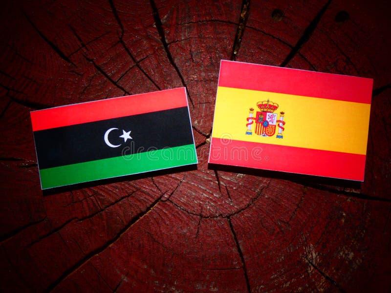 Bandera libia con la bandera española en un tocón de árbol fotos de archivo