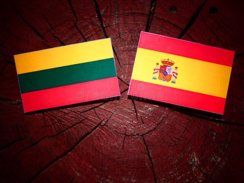 Bandera lituana con la bandera española en un tocón de árbol fotos de archivo