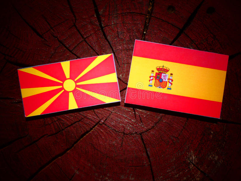 Bandera macedónica con la bandera española en un tocón de árbol imágenes de archivo libres de regalías