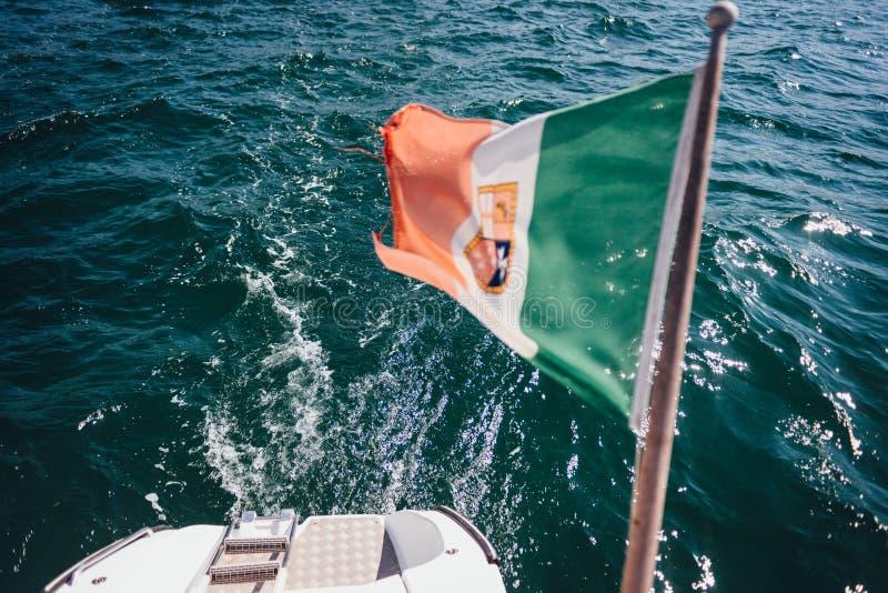Bandera marina italiana sobre la popa del yate imagen de archivo