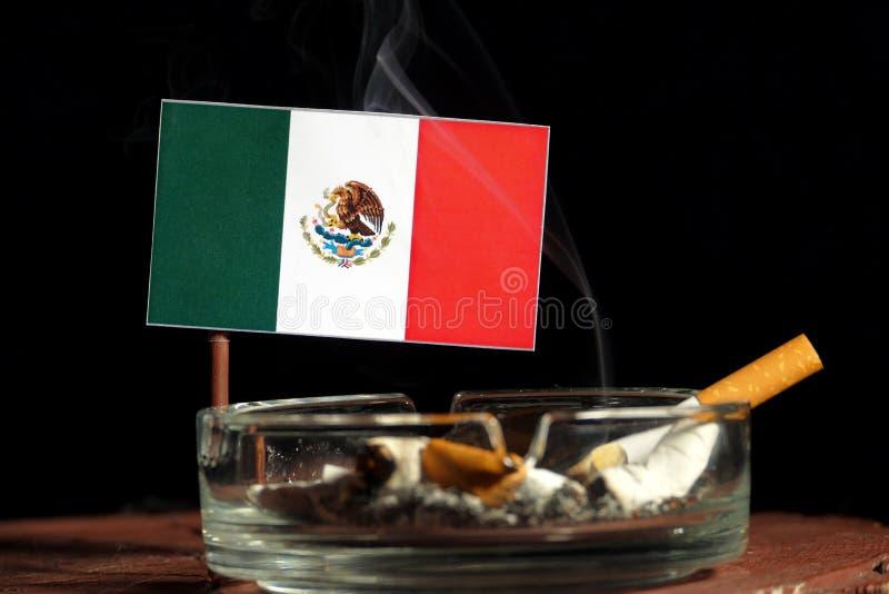 Bandera mexicana con el cigarrillo ardiente en el cenicero aislado en negro foto de archivo libre de regalías