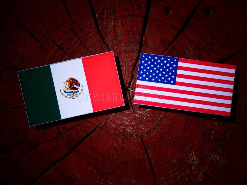 Bandera mexicana con la bandera de los E.E.U.U. en un tocón de árbol fotografía de archivo