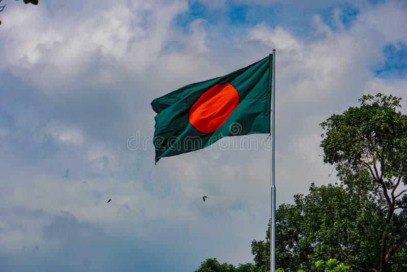 Bandera nacional de Bangladesh. La bandera verde roja ondea en el cielo azul de Bengala imagenes de archivo