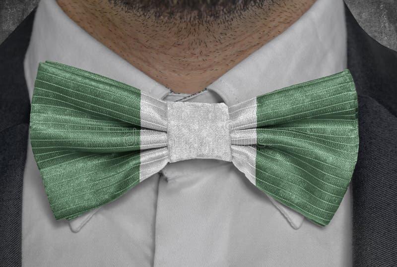 Bandera nacional de Nigeria en el traje del hombre de negocios del bowtie foto de archivo