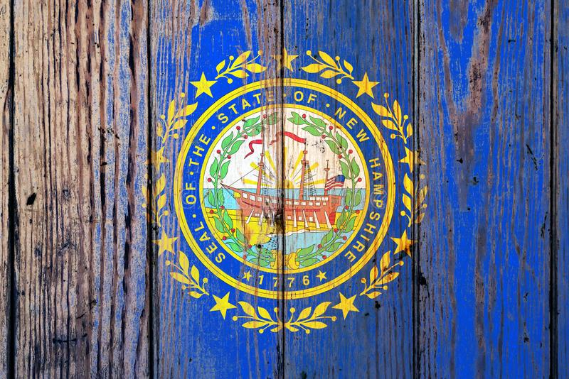 Bandera nacional del estado de New Hampshire los E.E.U.U. en un fondo gris de tableros de madera en el día de la independencia en imágenes de archivo libres de regalías