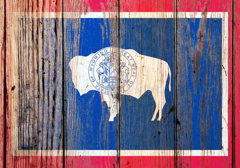 Bandera nacional del estado de Wyoming los E.E.U.U. en un fondo gris de tableros de madera en el día de la independencia en diver fotografía de archivo