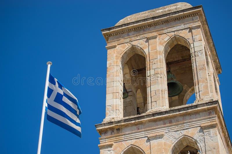 Bandera nacional griega y ruinas de la iglesia vieja con el cielo soleado azul en el fondo imagenes de archivo