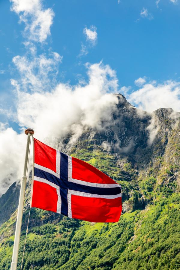 Bandera nacional noruega que agita en el viento y el mountain& x27; pico de s en el fiordo de Neroy, Aurlan, condado de Fjordane  fotografía de archivo