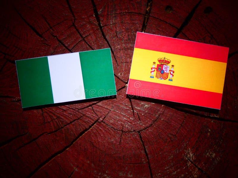 Bandera nigeriana con la bandera española en un tocón de árbol fotos de archivo libres de regalías