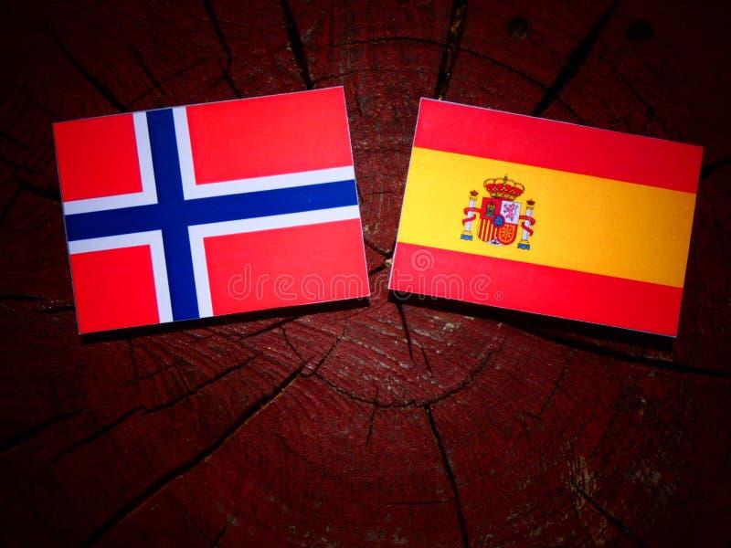 Bandera noruega con la bandera española en un tocón de árbol imagenes de archivo