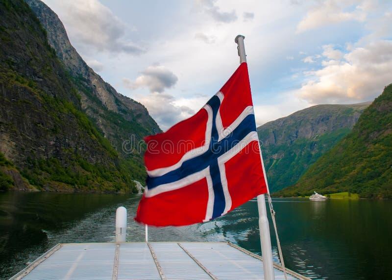 Bandera noruega en un barco dentro del paisaje de la montaña rocosa de Sognefjord fotos de archivo