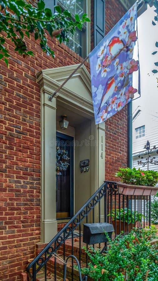Bandera ornamental delante de casas americanas típicas foto de archivo libre de regalías