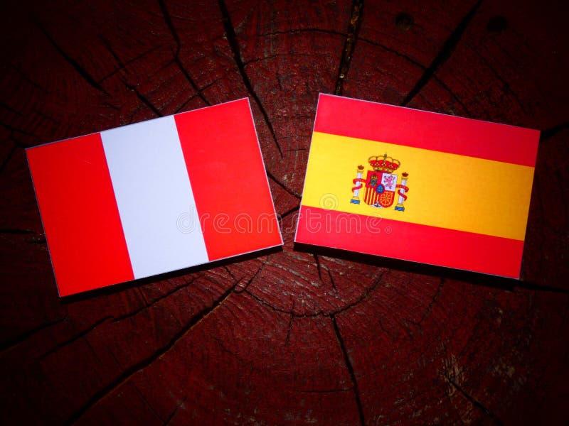 Bandera peruana con la bandera española en un tocón de árbol fotos de archivo