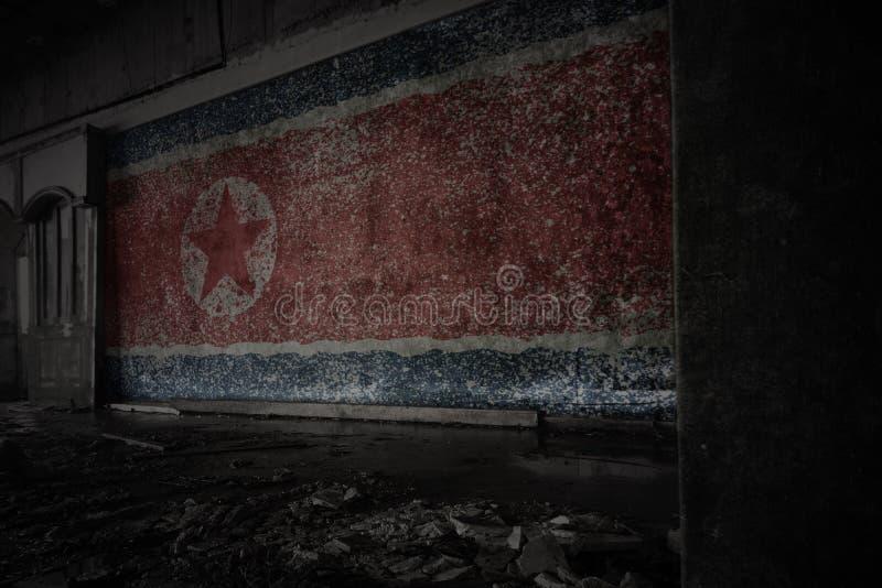 Bandera pintada de Corea del Norte en la pared vieja sucia en una casa arruinada abandonada fotos de archivo