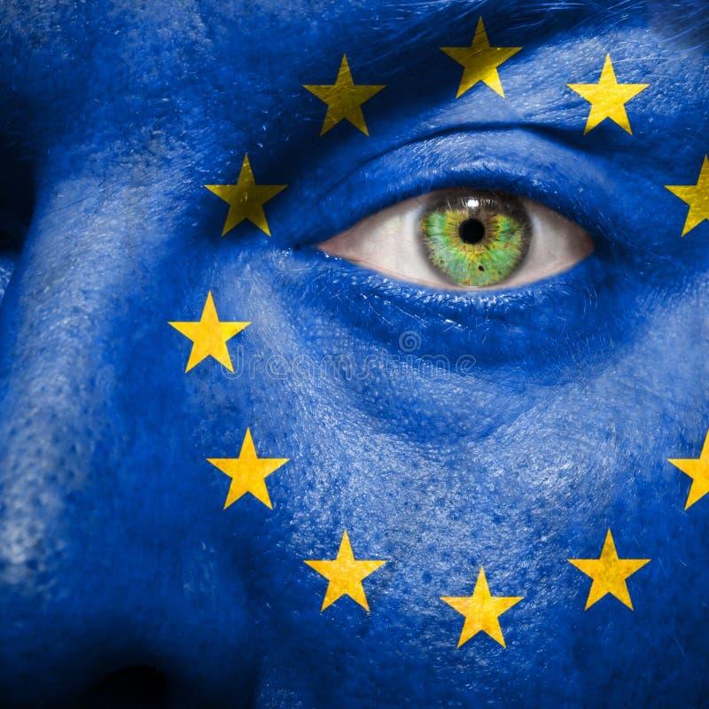 Bandera pintada en cara con el ojo verde para mostrar la ayuda de Europa imágenes de archivo libres de regalías