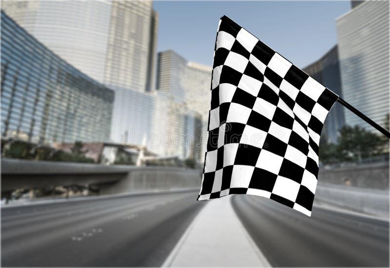 Bandera que agita a cuadros en fondo de la ciudad Concepto foto de archivo