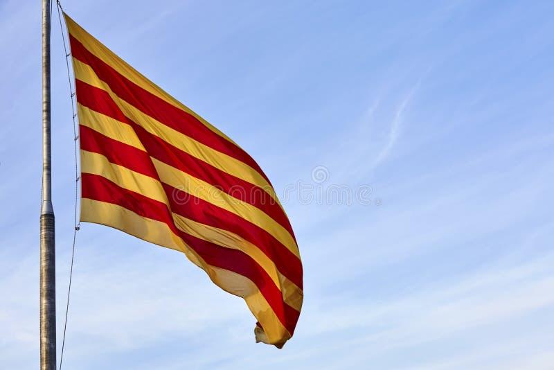 Bandera que agita del Catalunya Cataluña en el fondo del cielo azul Bandera de Cataluña que agita contra el cielo azul claro fotos de archivo