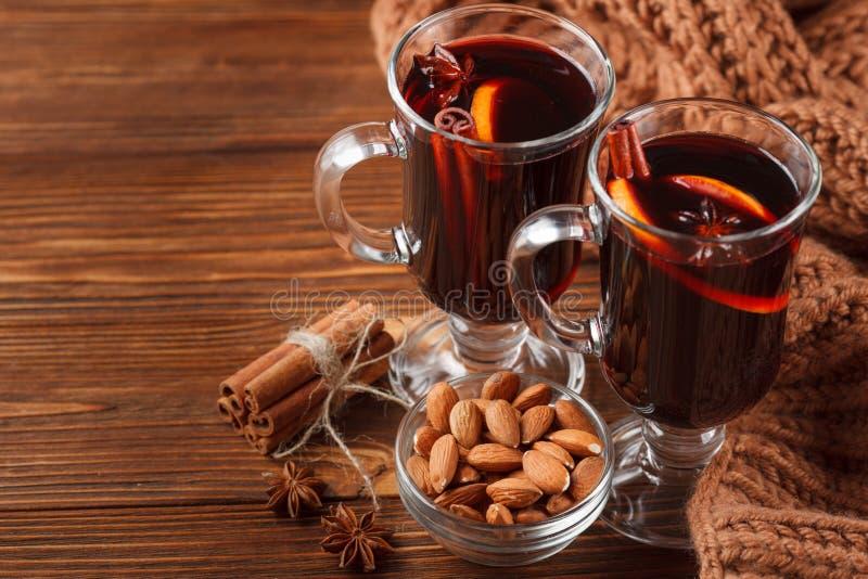 Bandera reflexionada sobre horizontal del vino del invierno Vidrios con el vino rojo y las especias calientes en fondo de madera foto de archivo libre de regalías