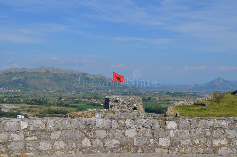Bandera roja albanesa con un águila doble-dirigida negra en la fortaleza de Rozafa Shkodra, Albania imágenes de archivo libres de regalías