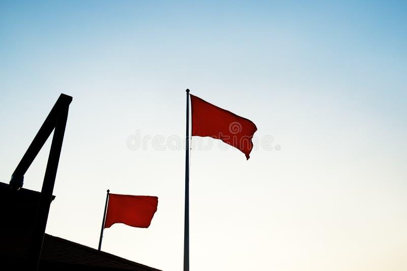 Bandera roja en un fondo del cielo azul marino imagenes de archivo