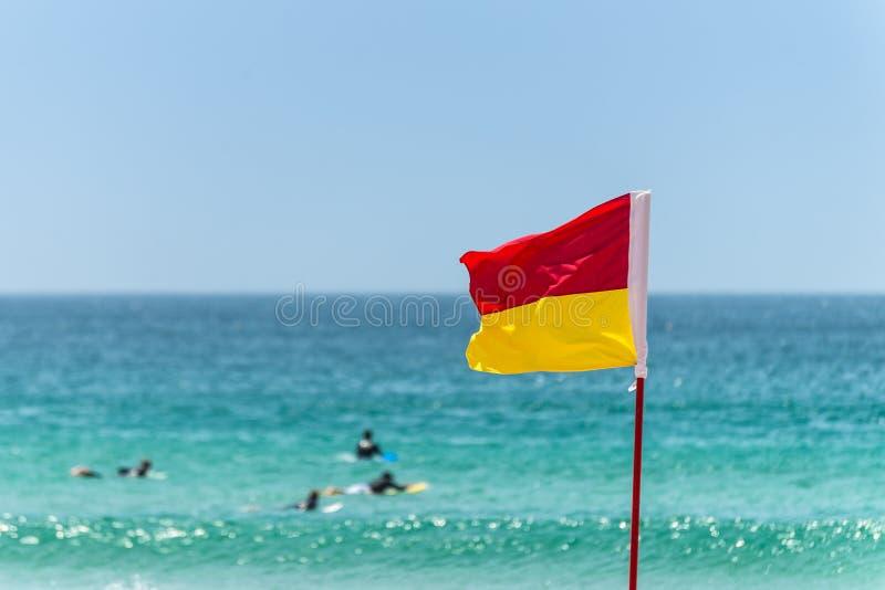 Bandera roja y amarilla de la señal de peligro en la playa imágenes de archivo libres de regalías