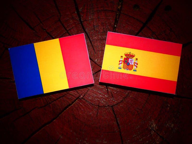 Bandera rumana con la bandera española en un tocón de árbol imagen de archivo