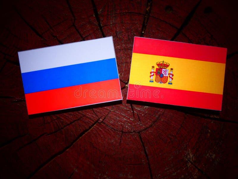 Bandera rusa con la bandera española en un tocón de árbol imagenes de archivo