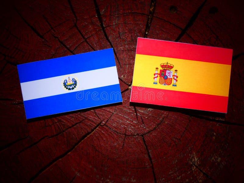 Bandera salvadoreña del EL con la bandera española en un tocón de árbol foto de archivo