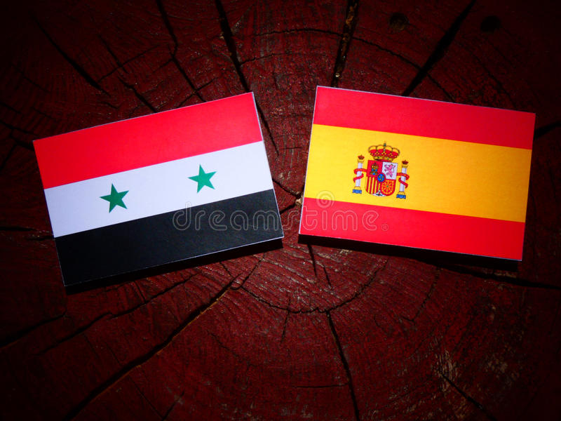 Bandera siria con la bandera española en un tocón de árbol fotografía de archivo