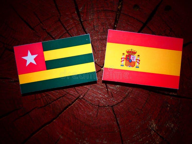 Bandera togolesa con la bandera española en un tocón de árbol fotografía de archivo