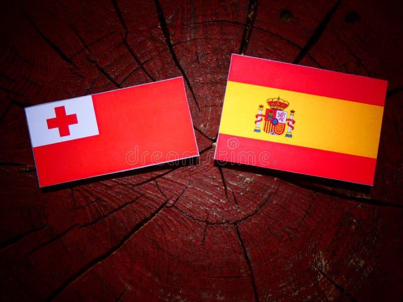 Bandera tongana con la bandera española en un tocón de árbol imagenes de archivo