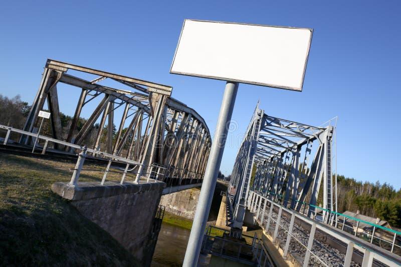 Bandera vacía en blanco delante del puente viejo del ferrocarril ningún trespassin fotos de archivo