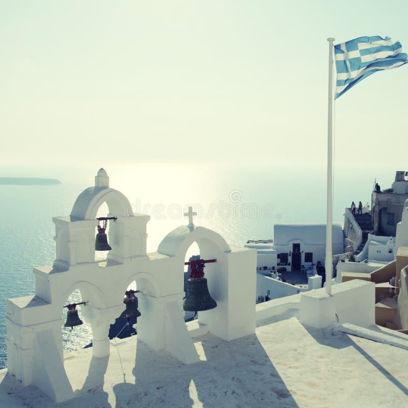 Bandera y campanario griegos en el pueblo de Oia, Santorini, Grecia imagenes de archivo