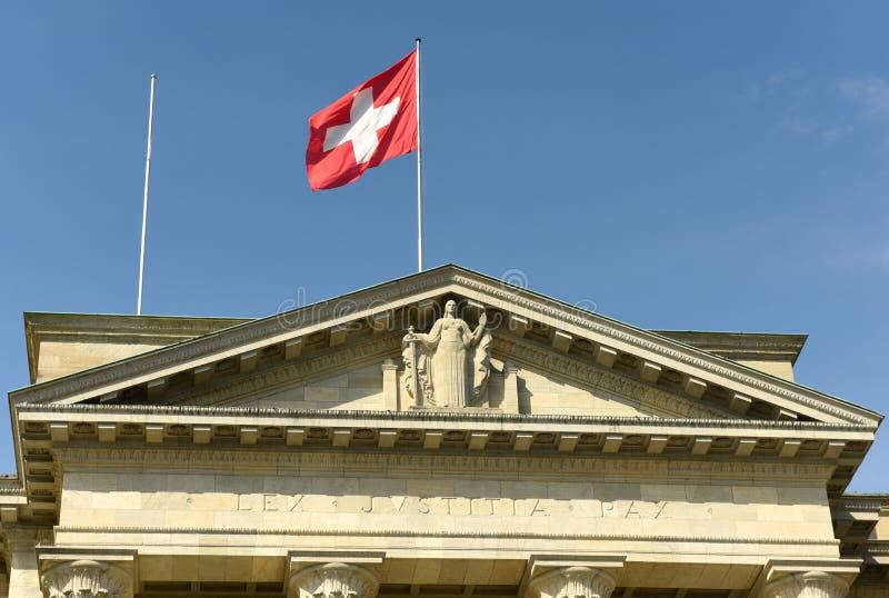 Bandera y estatua suizas de la justicia en el Tribunal Supremo federal de Swi foto de archivo libre de regalías