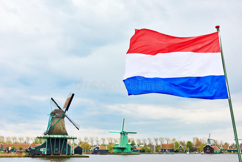 Bandera y molino de viento holandeses en el canal fotos de archivo