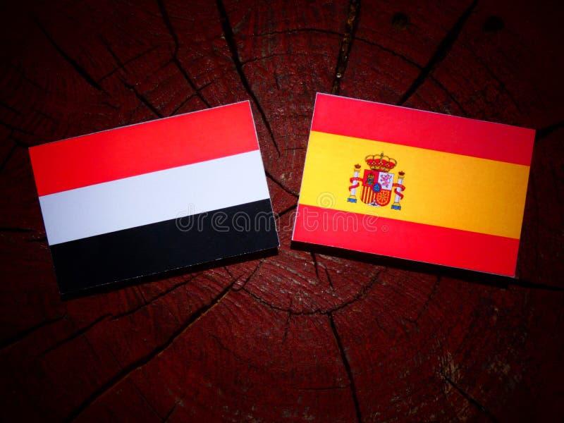 Bandera yemení con la bandera española en un tocón de árbol fotografía de archivo
