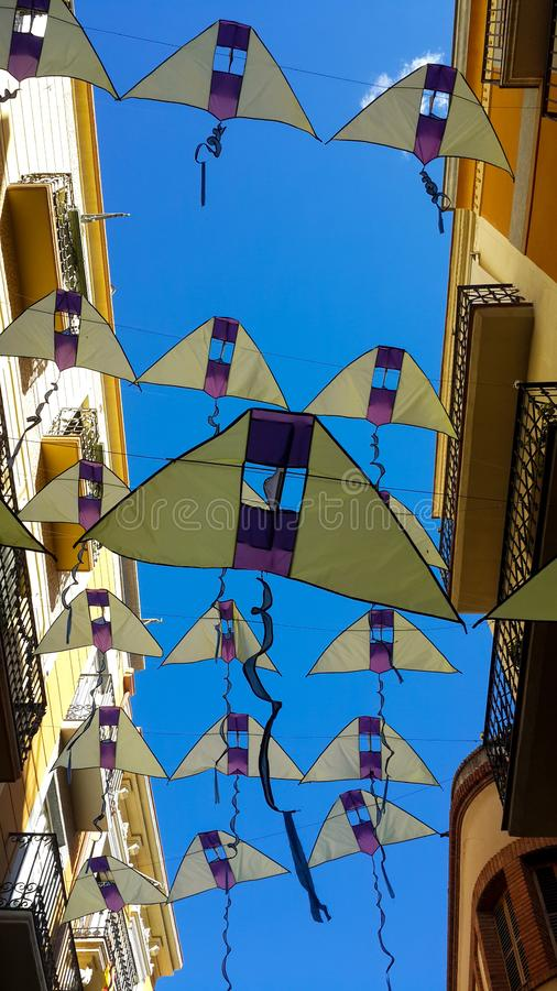 Banderas bajo la forma de cometas amarillas contra un cielo azul brillante, Reus, España imagenes de archivo