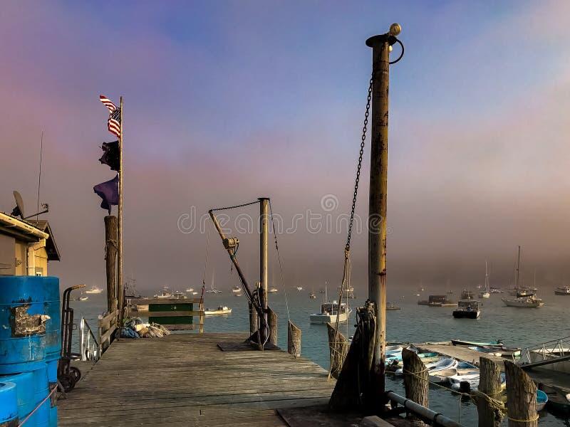 Banderas, barcos y niebla en Maine Harbor foto de archivo libre de regalías