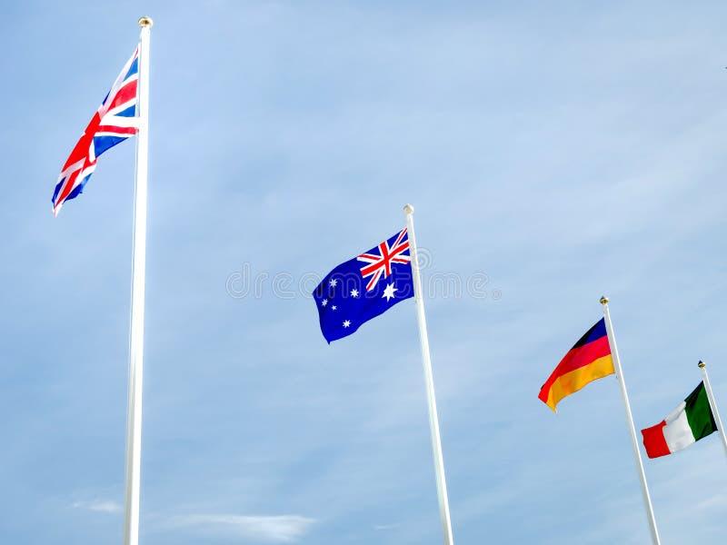 Banderas británicas, australianas, alemanas e irlandesas en asta de bandera foto de archivo