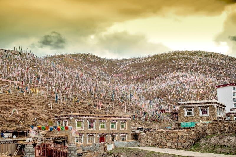 Banderas budistas coloridas del rezo en las montañas tibetanas de China imagen de archivo
